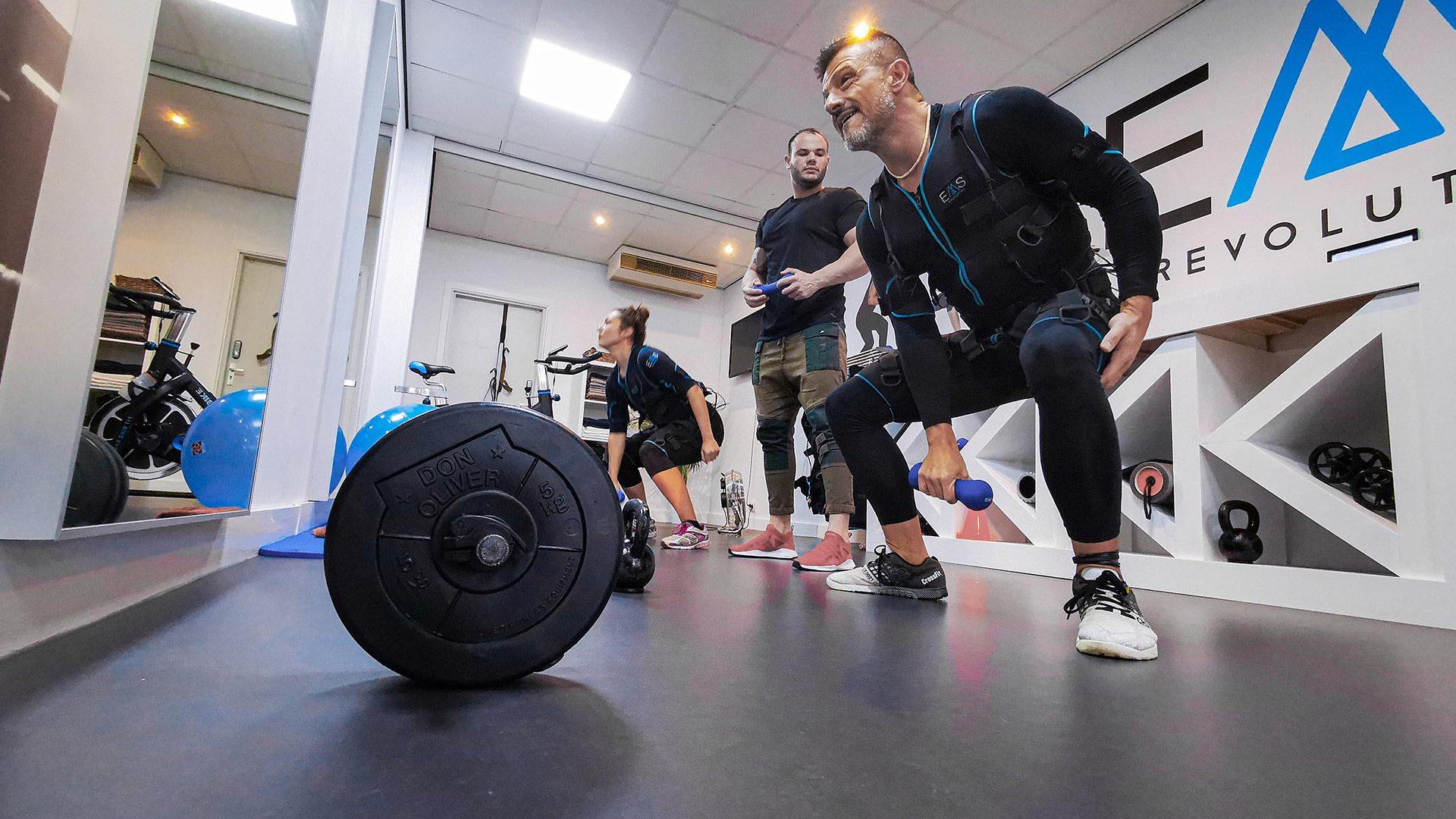 Twee sporters die een EMS Training volgen onder leiding van een personal trainer