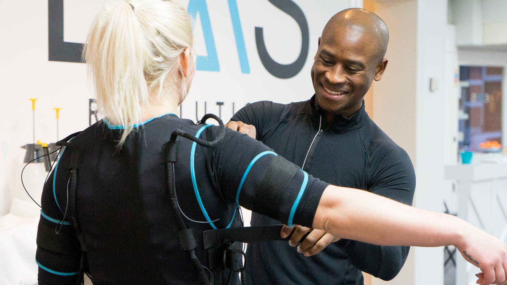 Vrouw die een EMS Pak aan heeft, de personal trainer zorgt ervoor dat het pak op maat wordt ingesteld.