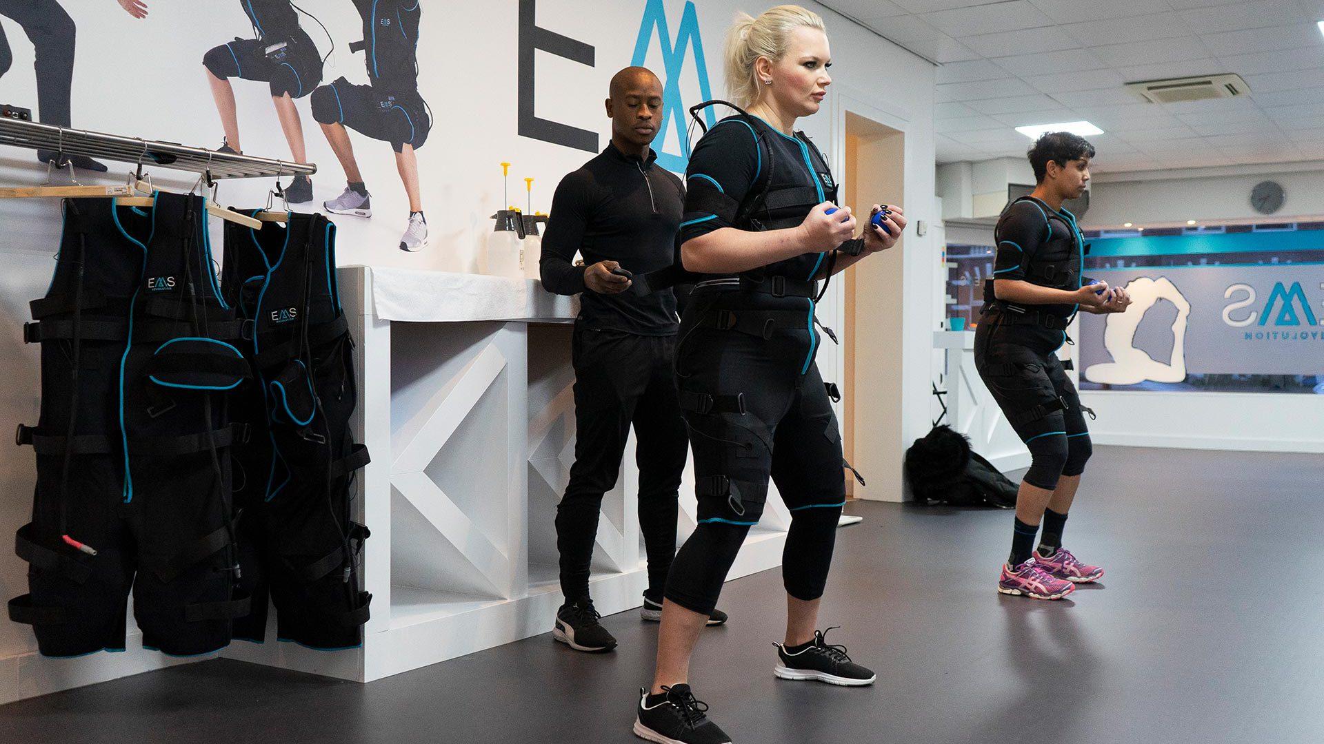 Twee sporters die een EMS Training volgen, de personal trainer verhoogt de impulsfrequentie.