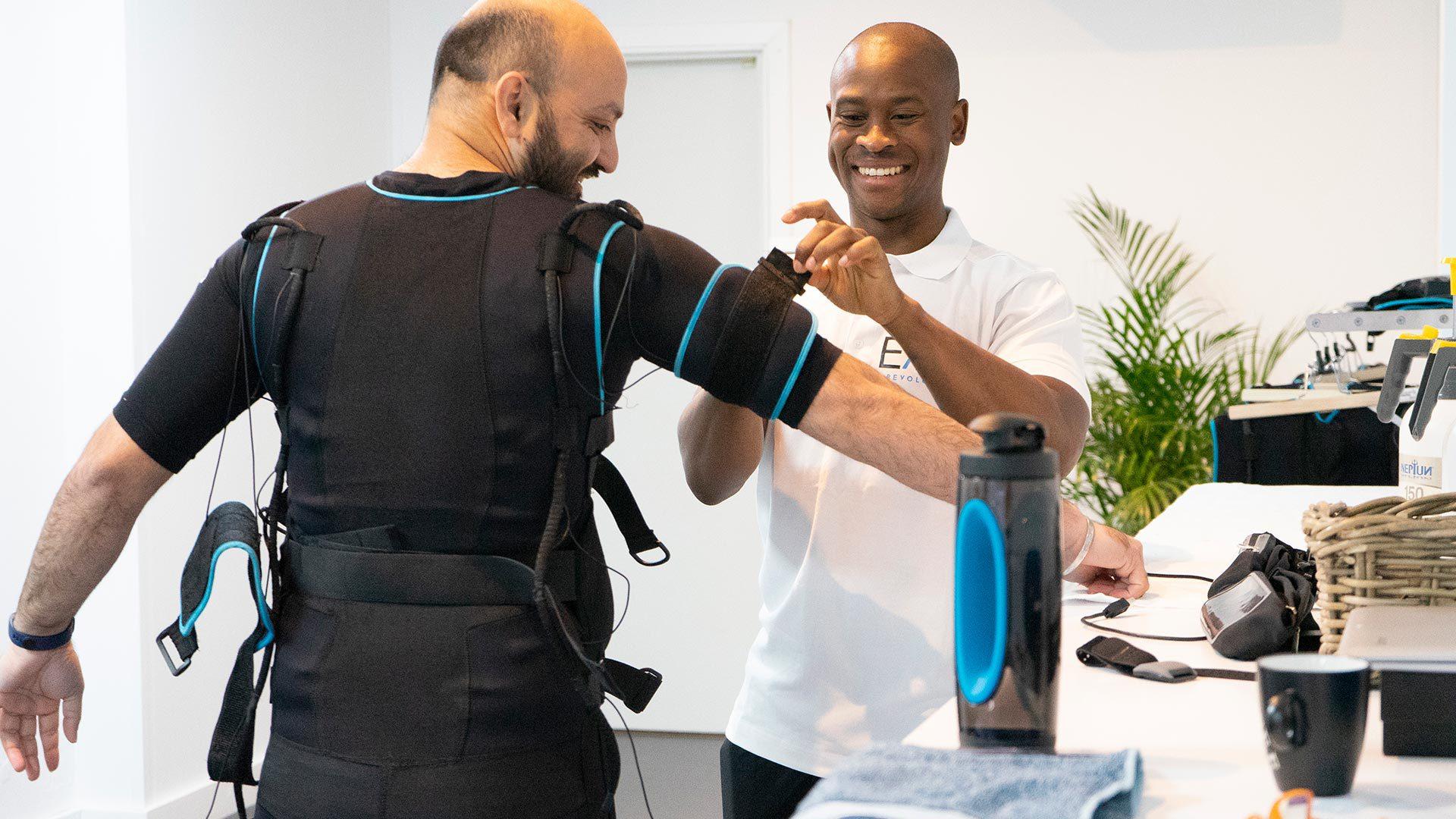 Man die een EMS Pak aan heeft, de personal trainer zorgt ervoor dat het pak op maat wordt ingesteld.